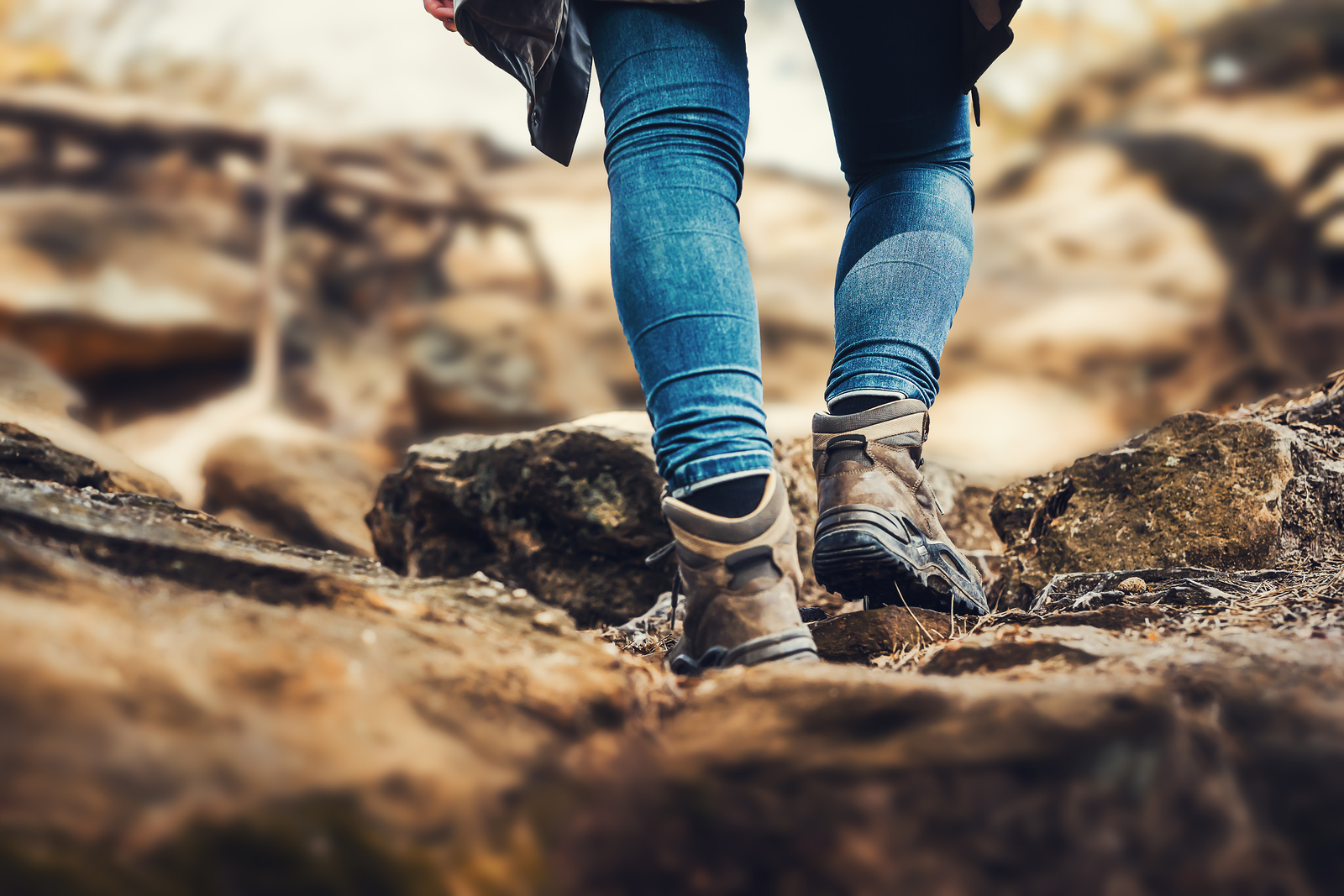 Person is hiking a hill – hiking shoes from behind on a hiking trail